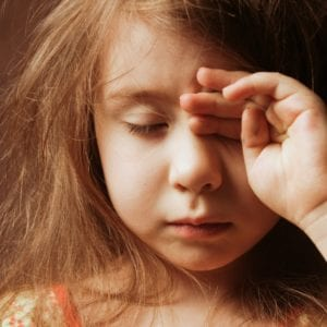 Sleepy girl rubbing her eye