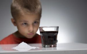 Child looking at glass of soda next to pile of sugar